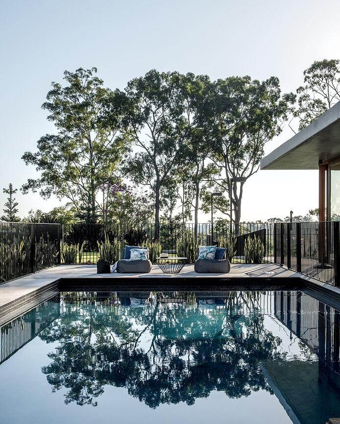 Brisbane luxury home builder Kalka | pool with pool chairs and gumtrees in background