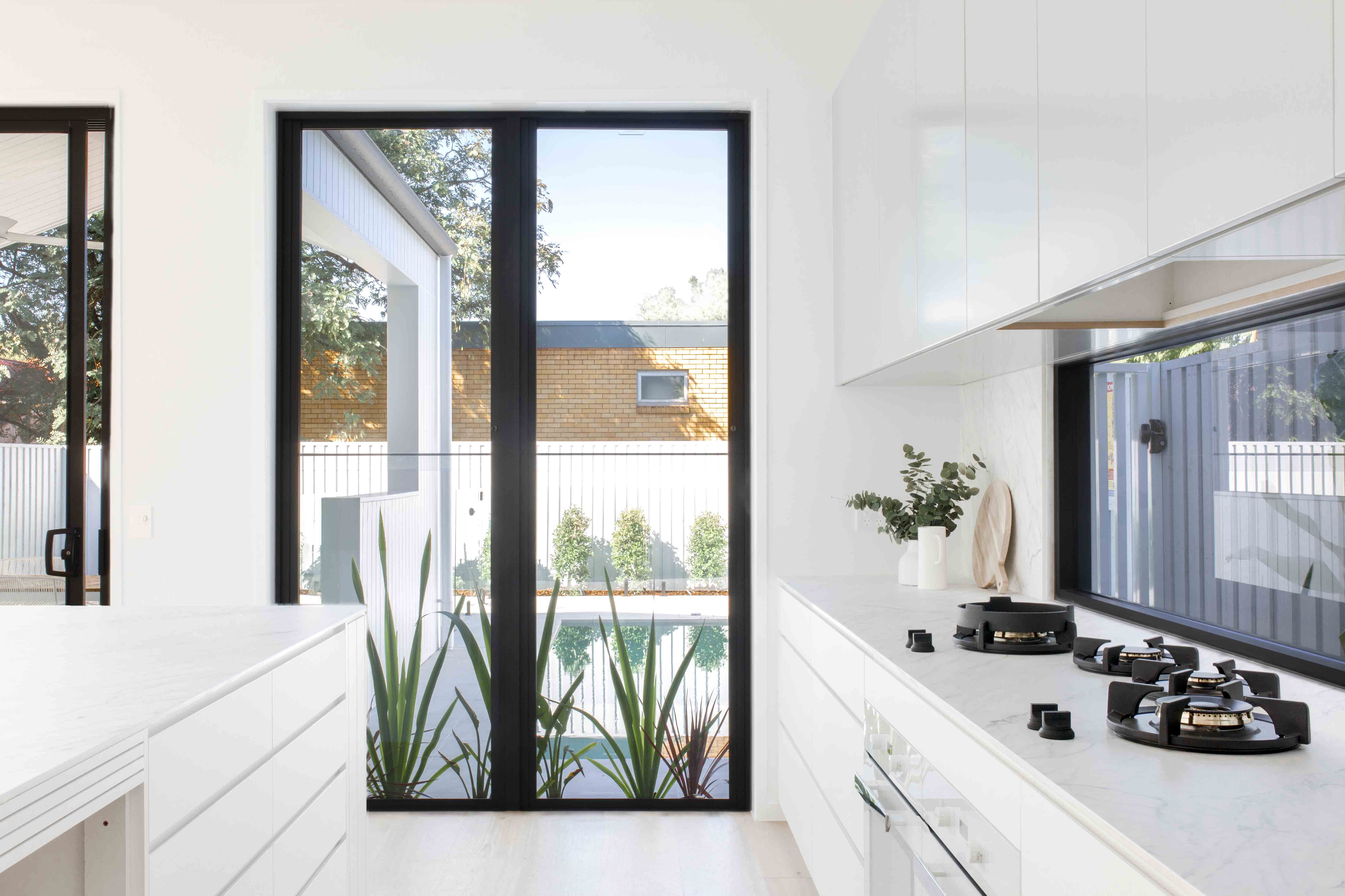 Kalka Clayfield display home porcelain benchtops in the kitchen, looking out to the inground swimming pool