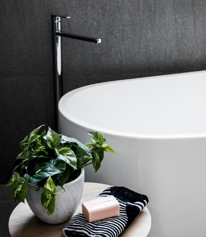 Brisbane luxury home builder Kalka | Free standing bath with side table featuring green plant and soap | Rochedale display home