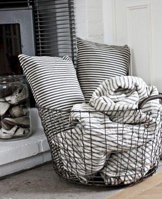 Wire basket holding striped throw and two cushions