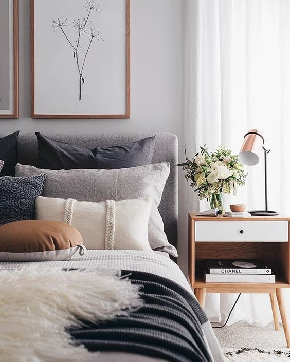 Grey fabric bed with cushions and a timber side table