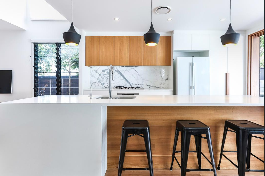 Modern kitchen featuring 2PAC cupboards and doors with blackbutt veneer overhead cupboards, designed and built by Kalka.